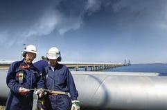 Trabajadores del aceite con la tubería principal gigante Foto de archivo libre de regalías