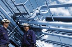 Trabajadores del aceite y tuberías de la refinería imagenes de archivo