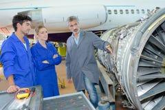 Trabajadores del aeropuerto con el aeroplano en fondo fotografía de archivo libre de regalías