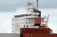Trabajadores del buque de carga que descargan los envases en puertos de Auckland Imagen de archivo libre de regalías