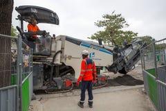 Trabajadores del camino con una máquina moderna en París, Francia foto de archivo