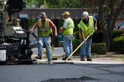 Trabajadores del camino que rastrillan el asfalto caliente Imagen de archivo