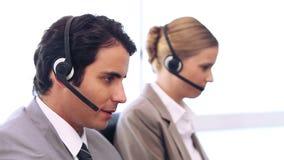 Trabajadores del centro de llamada que hablan en las auriculares almacen de metraje de vídeo