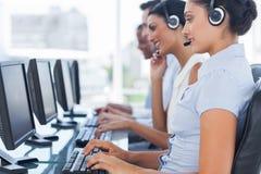 Trabajadores del centro de llamada que se sientan en línea mientras que ayuda a gente foto de archivo