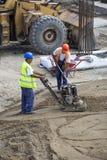 Trabajadores del constructor con la placa vibrante Imagen de archivo