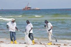 Trabajadores del derramamiento de petróleo en la costa Fotografía de archivo libre de regalías