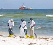 Trabajadores del derramamiento de petróleo que limpian la playa Imagenes de archivo