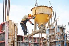 Trabajadores del edificio que vierten el hormigón con el barril Imágenes de archivo libres de regalías