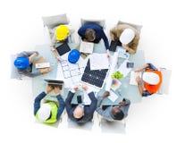 Trabajadores del emplazamiento de la obra en la mesa de reuniones Imágenes de archivo libres de regalías