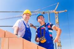 Trabajadores del emplazamiento de la obra que construyen la casa con la grúa Imagen de archivo