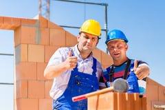 Trabajadores del emplazamiento de la obra que construyen las paredes en casa Imagenes de archivo