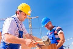 Trabajadores del emplazamiento de la obra que construyen las paredes en casa Foto de archivo libre de regalías