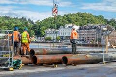 Trabajadores del emplazamiento de la obra que mueven los tubos enormes Foto de archivo