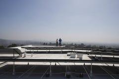 Trabajadores del mantenimiento cerca de los paneles solares en tejado imagen de archivo