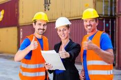 Trabajadores del naviera delante de los envases Foto de archivo libre de regalías