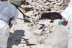 Trabajadores del petróleo en la playa Imagen de archivo