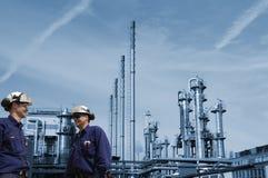 Trabajadores del petróleo y gas con la refinería imagenes de archivo