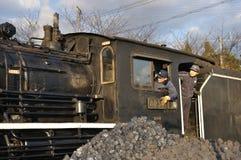 Trabajadores del tren que miran fuera de sitio de motor Imagenes de archivo