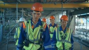 Trabajadores e ingenieros, caminando en fábrica industrial almacen de metraje de vídeo
