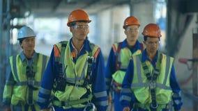 Trabajadores e ingenieros, caminando en fábrica industrial