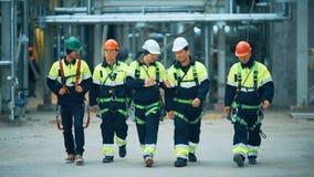 Trabajadores e ingenieros que caminan en fábrica industrial metrajes