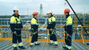Trabajadores e ingenieros que discuten en la refinería, escena industrial en fondo almacen de metraje de vídeo