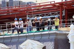 Trabajadores en el tejado de un edificio bajo construcción imágenes de archivo libres de regalías