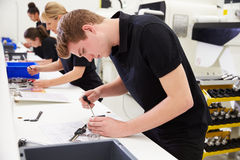Trabajadores en fábrica de ingeniería que comprueban calidad componente foto de archivo