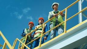 Trabajadores en la instalación de producción como equipo que discute, escena industrial en fondo metrajes