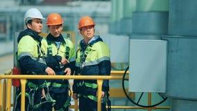 Trabajadores en la instalación de producción como equipo que discute, escena industrial en fondo almacen de video