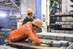 Trabajadores en la máquina en el secado de piedra de los bloques Fotos de archivo libres de regalías