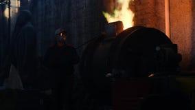 Trabajadores en la planta metalúrgica que trabaja con de fundición Cantidad com?n Los trabajadores en uniformes y cascos trabajan almacen de metraje de vídeo