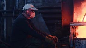 Trabajadores en la planta metalúrgica que trabaja con de fundición Cantidad com?n Los trabajadores en uniformes y cascos trabajan metrajes