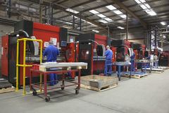 Trabajadores en las máquinas de funcionamiento del taller de la fabricación fotos de archivo