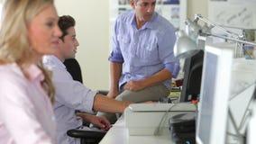 Trabajadores en los escritorios en oficina creativa ocupada almacen de metraje de vídeo