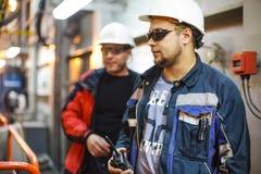 Trabajadores en ropa protectora y cascos blancos Un trabajador con Imagen de archivo