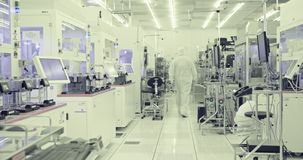 Trabajadores en sitio limpio en una instalación industrial de los semiconductores metrajes