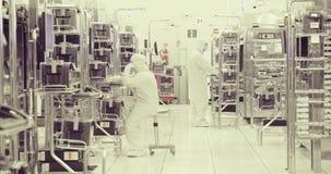 Trabajadores en sitio limpio en una instalación industrial de los semiconductores almacen de video