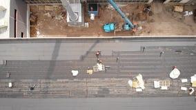 Trabajadores en un emplazamiento de la obra El proceso del aislamiento hidráulico del tejado Con la ayuda de un material especial almacen de video