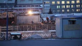 Trabajadores en un emplazamiento de la obra por la tarde en la ciudad rusa metrajes