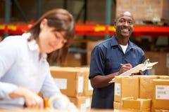 Trabajadores en Warehouse que prepara las mercancías para el envío Imagen de archivo