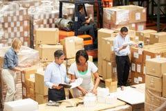 Trabajadores en Warehouse que prepara las mercancías para el envío imagenes de archivo