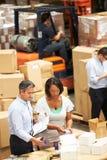 Trabajadores en Warehouse que prepara las mercancías para el envío imagen de archivo libre de regalías