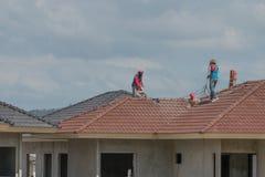 Trabajadores expertos que tejan en tejado de una nueva casa fotos de archivo