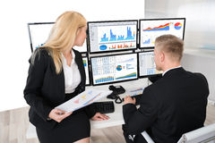 Trabajadores financieros que analizan gráficos en los ordenadores en oficina Fotos de archivo