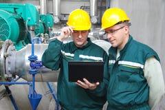 Trabajadores industriales con el cuaderno Imagen de archivo libre de regalías