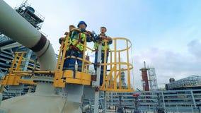 Trabajadores industriales e ingenieros que se colocan en frente de la torre de la fábrica grande almacen de video