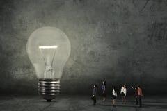 Trabajadores jovenes que miran la lámpara brillante Imagen de archivo libre de regalías