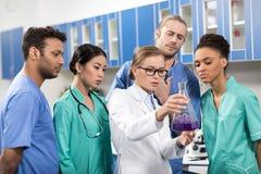 Trabajadores médicos enfocados anakyzing el tubo de ensayo en laboratorio foto de archivo