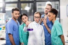 Trabajadores médicos que analizan el tubo de ensayo en laboratorio foto de archivo